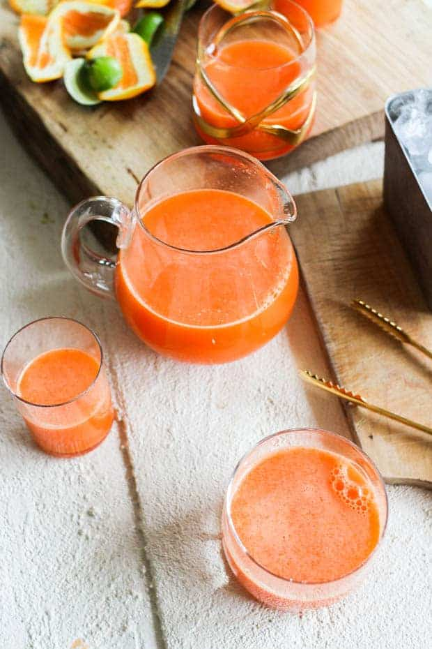 3 glasses of orange immune boost juice and a small glass pitcher on a table with citrus peels