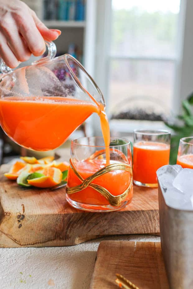 Immune boost juice being poured from a pitcher into a glass next to a metal dish of ice.
