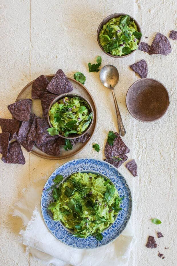A big blue bowl filled with guacamole topped with fresh herbs. 3 smaller serving sized bowls are placed around it on the table . There is a shallow bowl of purple corn chips next to the guac. n