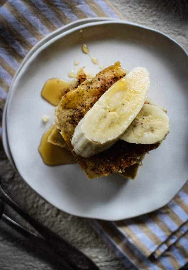 2 squares of roasted banana chai sheet pan pancake topped with fresh banana slices and maple syrup