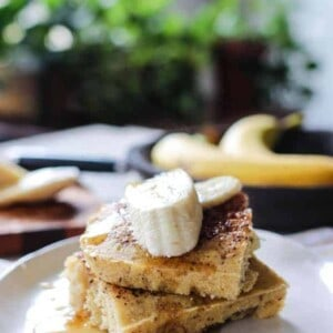 A plate with 2 slices of roasted banana chai sheet pan pancakes topped with maple syrup and fresh banana slices.