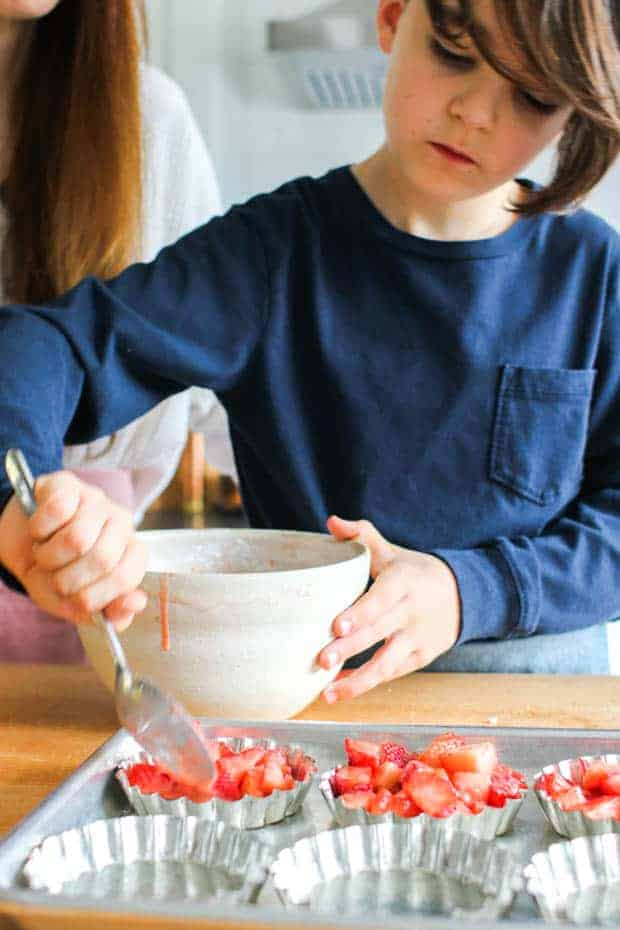 A boy scooping strawberries into mini baking pans.