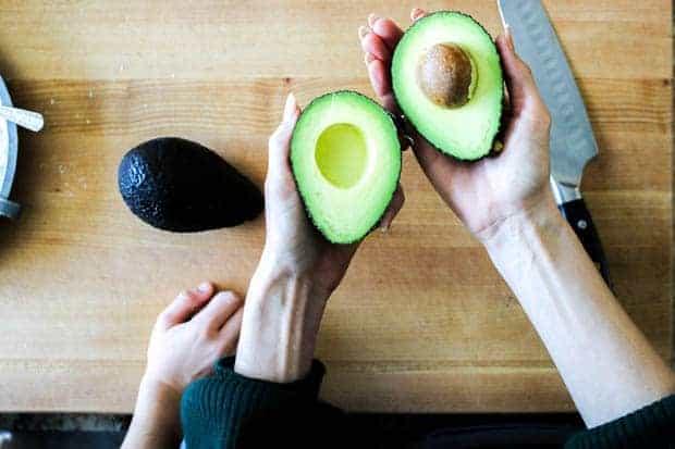 A wan holding a halved avocado