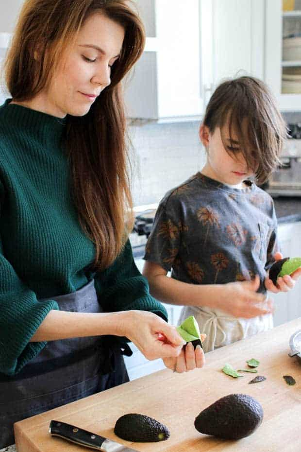 A woam showing a young boy how to peel an avocado