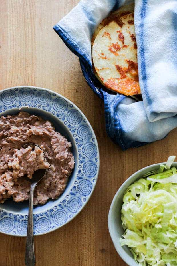 A bowl of refried beans, a bowl of shredded lettuce, and a basket of cheddar cheese 'frico' tortillas