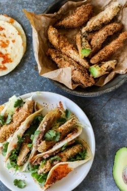 A platter full of Crunchy Gluten Free Avocado Taco s is next to a serving dish that is full of crispy golden avocado wedges