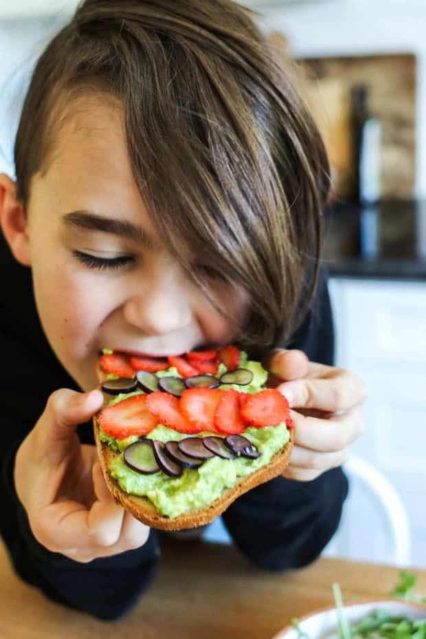 A boy eating a slice of fruity avocado toast