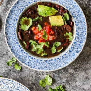 Bowls of Instant Pot Black Bean Soup topped with avocado, cilantro, and pico de gallo