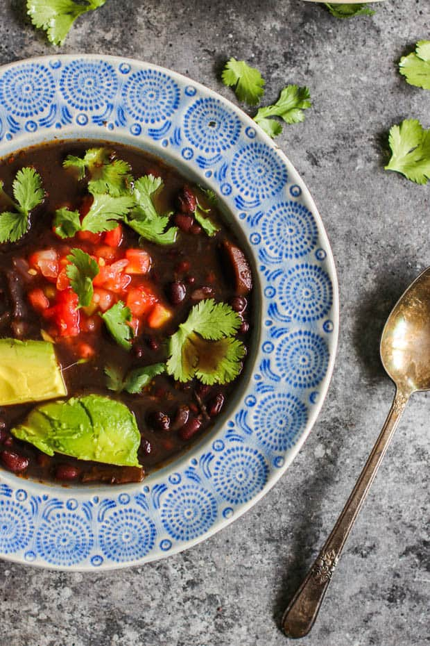 A close up of a bowl of Instant Pot Black Bean Soup topped with salsa, avocado, and cilantro leaves