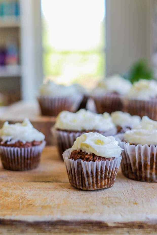 8 Easy Gluten Free Carrot Cake Muffins on a wooden table in front of a window.