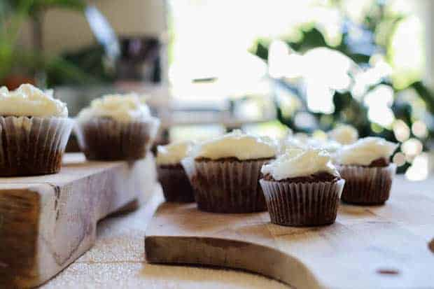 A table full of iced Gluten Free Carrot Cake Muffins
