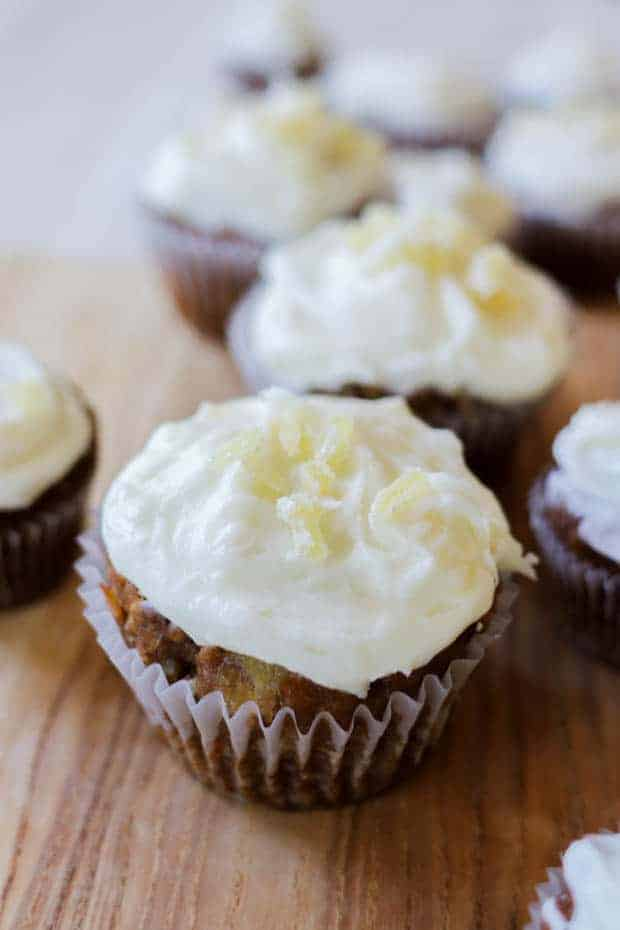 Close up of iced Easy Gluten Free Carrot Cake Muffins with cream cheese frosting and iced candied ginger garnishes