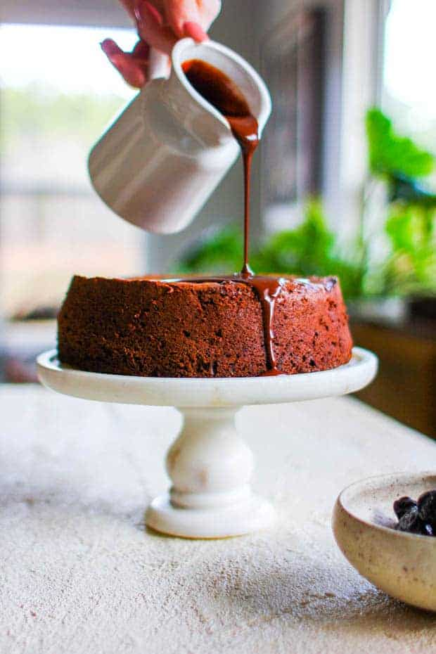 Chocolate ganache icing being poured onto a Chocolate Covered Prune Fudge Cake