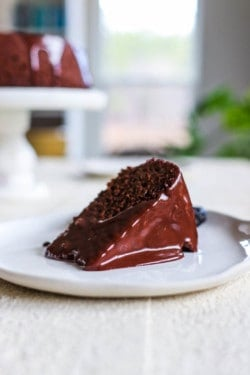 A slice of Chocolate Covered Prune Fudge Cake on a plate in front of the rest of the cake on a cake stand