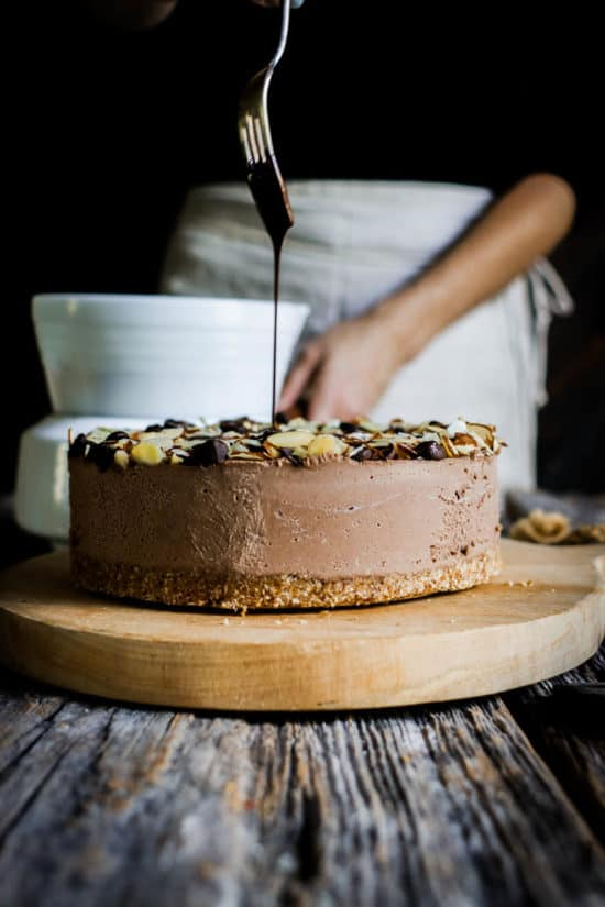 A woman drizzling chocolate over an icebox cake