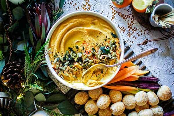 A bowl of Roasted Butternut Hummus with Crispy Fried Sage sprinkled over the top served with brazilian cheese bread and rainbow carrots