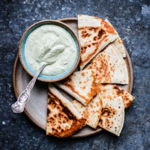 A plate filled with quesadilla wedges and a bowl of Roasted Poblano Cashew Cream Sauce.