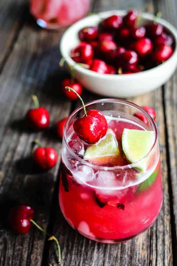 A bright red Fresh Cherry Limeade Cocktail garnished with lime quarters and fresh cherries on a table next to a bowl of fresh cherries