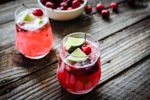 2 Fresh Cherry Limeade cocktails next to a bowl of fresh cherries