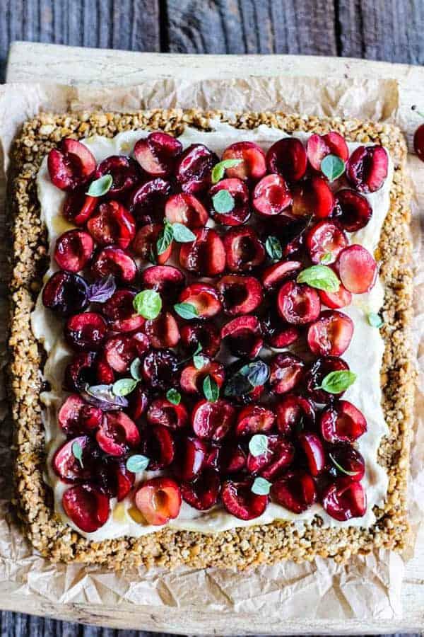 An entire Gluten Free Fresh Cherry Pretzel Tart on a wood cutting board