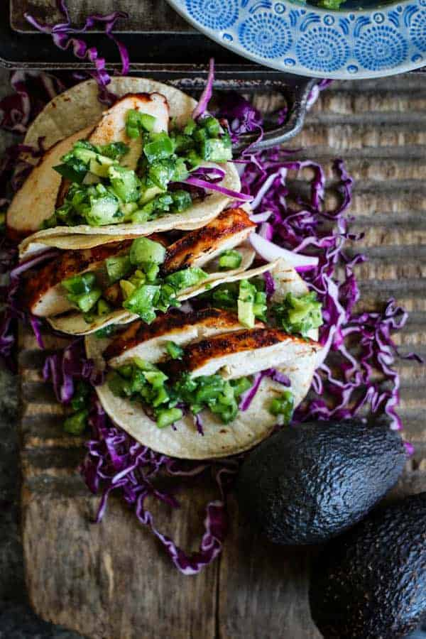 Three grilled chicken tacos piled high with verde pico de gallo and shredded red cabbage