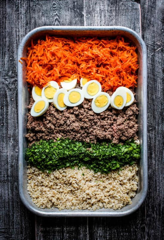 All of the ingredients for homemade dog food in a baking dish before being mixed together. Ground beef, brown rice, shredded carrot, chopped hard boiled eggs, and minced parsley