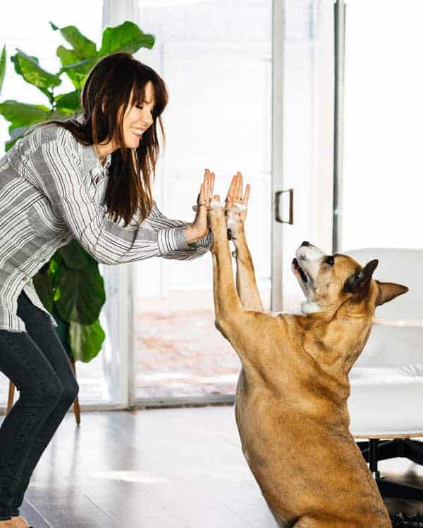 A woman and a dog going each other high fives