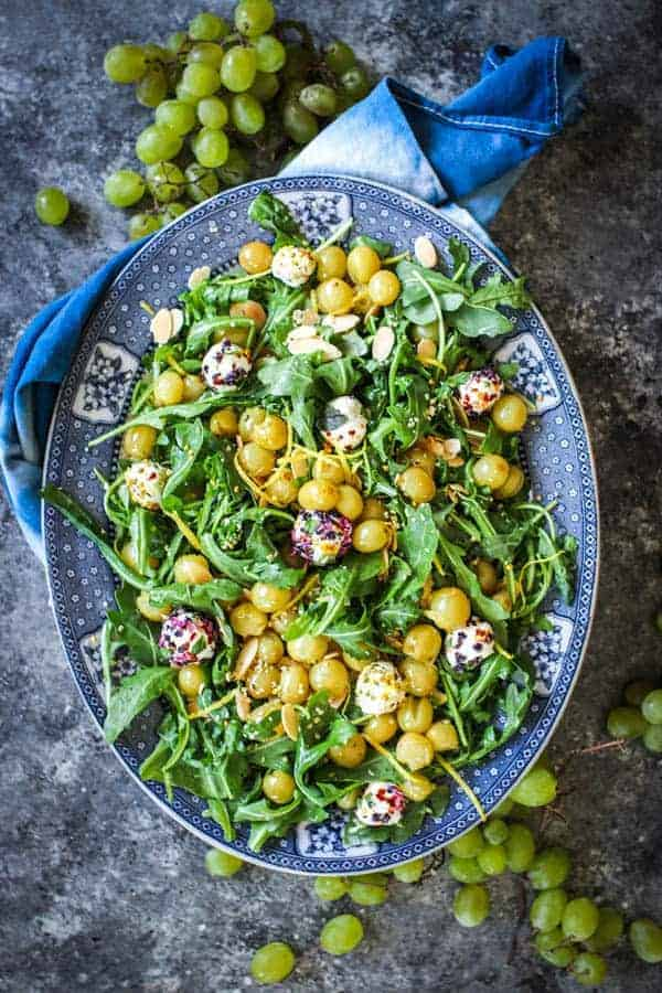 A platter filled with Roasted Grape & Arugula Salad