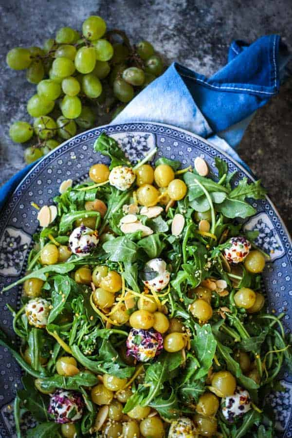 A platter filled with Roasted Grape & Arugula Salad - roasted green grapes, arugula, goat cheese balls rolled in edible flowers, and slivered almonds