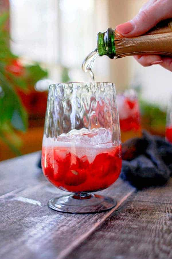 A woman pouring wine into a glass that has muddled strawberries and lemon juice