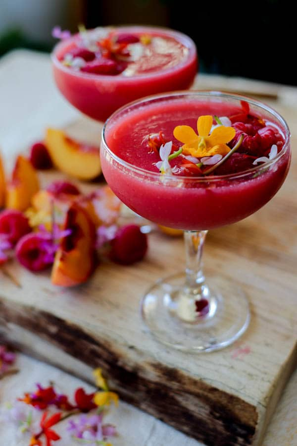 2 pink Raspberry Frosé Cocktails in coupe glasses topped with fresh raspberries and edible flower blossoms.