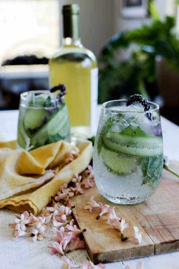 Two Cucumber Herb Spritzers sit on a table with a bottle of wine in teh background. The spritzers are garnished with thin strips of cucumber that wrap around the inside of the stemless wine glass, basil blossoms, and lime wheels