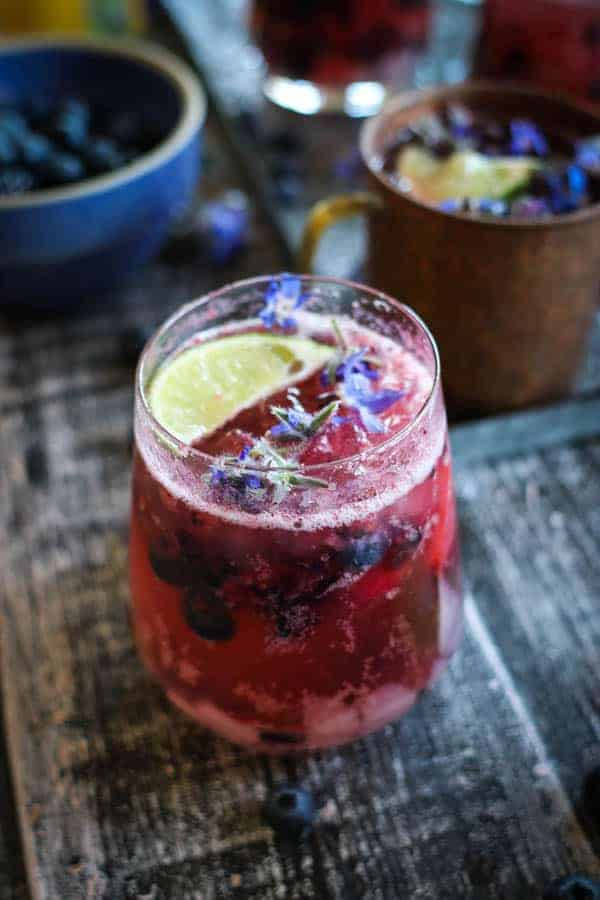 A Fresh Berry Muscato Mule in a stemless wine glass and one in a copper mug sit next to each other on a table. They are garnished with blueberries, blackberries and beautiful blue edible flowers.