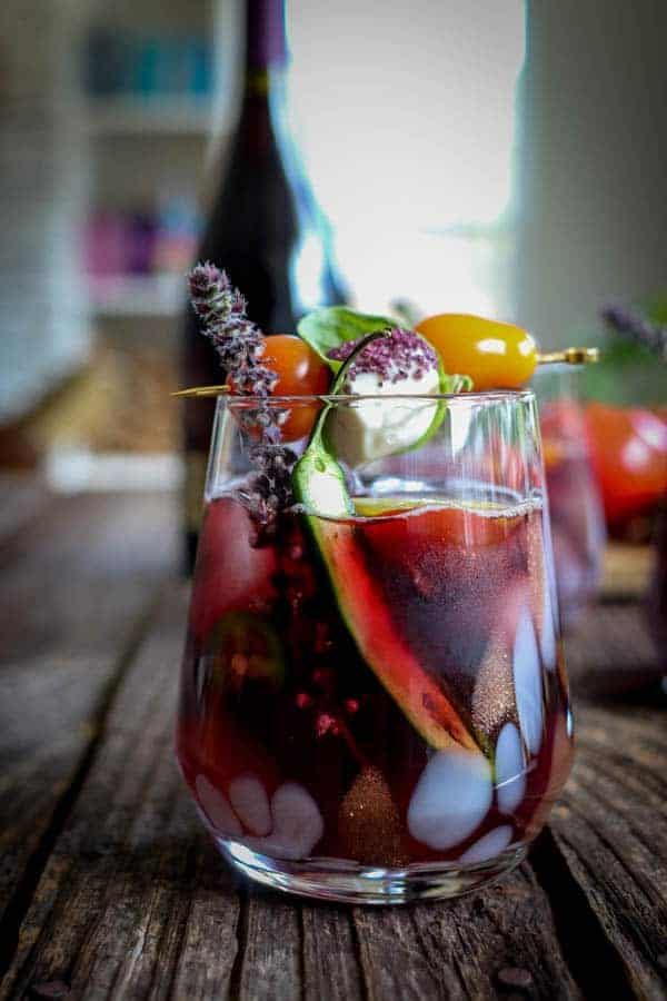 A Farmers Market Wine Cocktail in a stemless glass garnished with basil blossoms, mozzarella balls dipped in wine salt, cherry tomatoes, and a serrano pepper half on a table in front of a bottle of red wine.