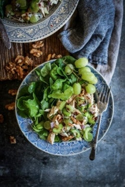 2 plates piled high with Easy Rotisserie Chicken Salad on top of butter lettuce leaves. The chicken salad has shredded rotisserie chicken, sliced green grapes, walnuts, celery, walnuts, and red onion toss din a Greek yogurt dressing