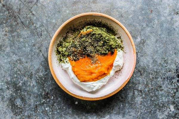 A Pumpkin and Yogurt Bowl for Dogs on a metal table top. It is layered with yogurt, pumpkin puree, vitamin powder, and herbs.