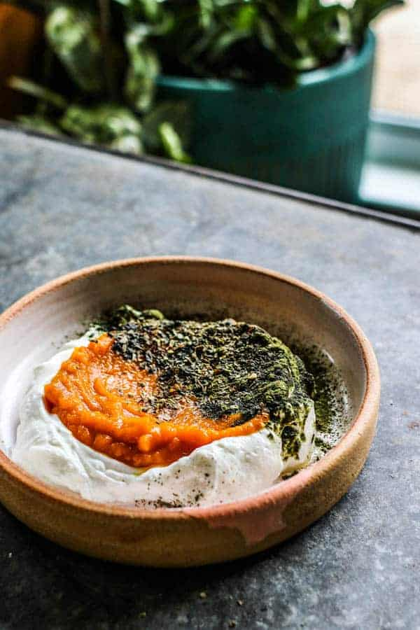 A Pumpkin and Yogurt Bowl for Dogs sits on a table. It is layered with greek yogurt, pumpkin puree, and a sprinkling of green vitamin powder and dried herbs