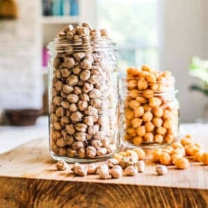 2 jars of chickpeas sitting on a table top - one has dried chickpeas and one has canned.