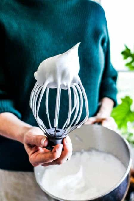 A woman in a green sweater holding a kitchen aid stand mixer bowl and whisk attachment with aquafaba on the end. She is showing that aquafaba whips up like egg whites.