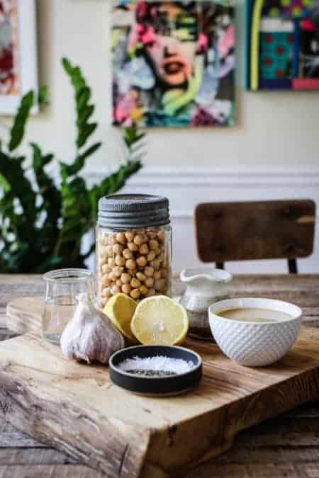 A wooden cutting board that has a lemon half, garlic bulb, a glass jar of chickpeas, and bowl of tahini on top.
