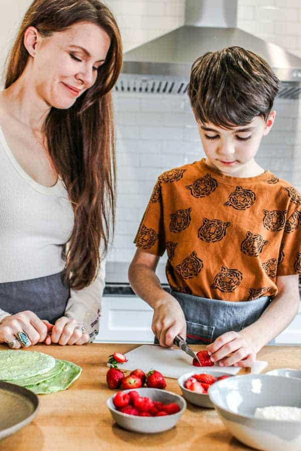 A mom watching as her son slices strawberries