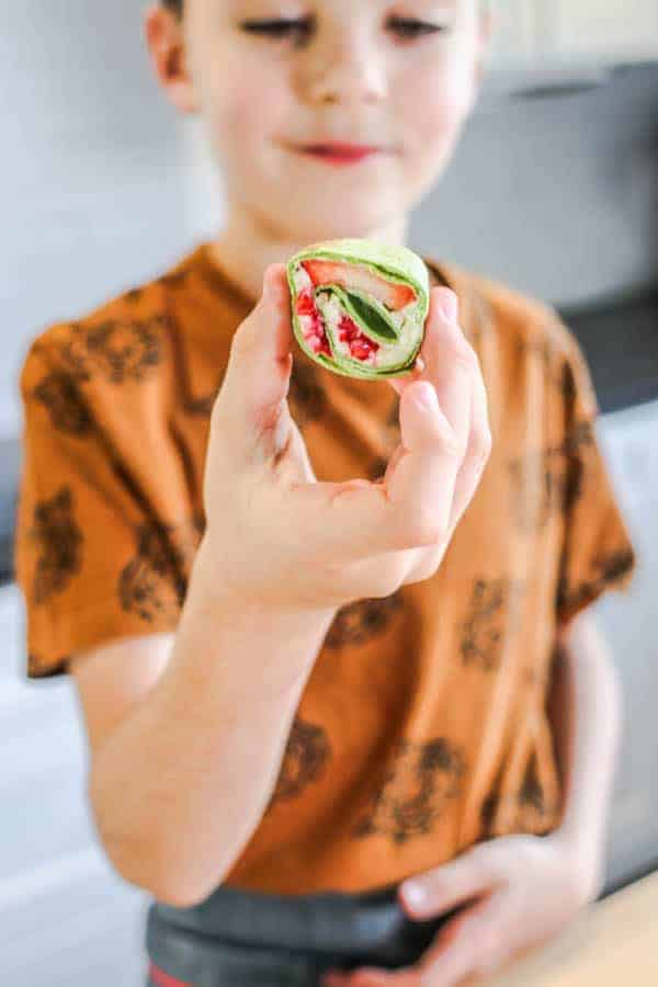 A little boy holding a Fresh Berries and Cream Roll Up
