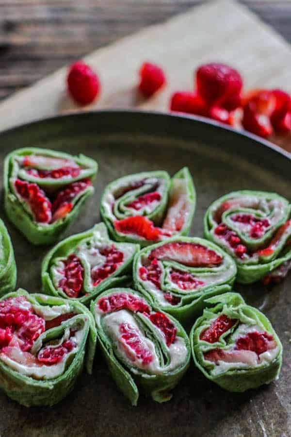 A plate of Easy Fresh Berries and Cream Roll Ups next to fresh raspberries