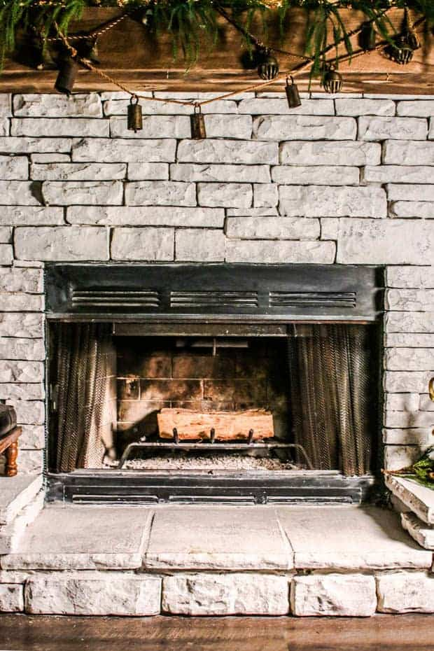 A fire place decorated for the holidays with a stack of wood inside it.