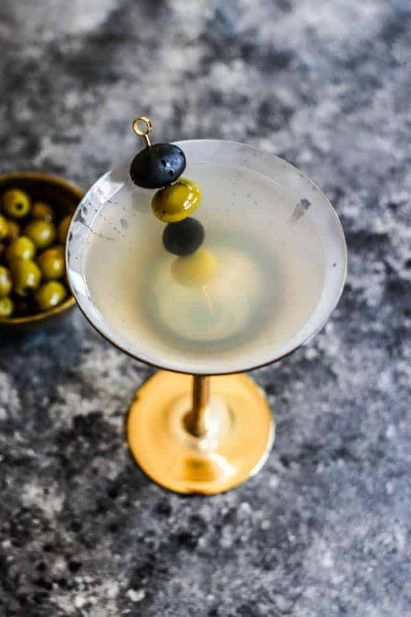 One Classic Vodka Martini next to a bowl of olives