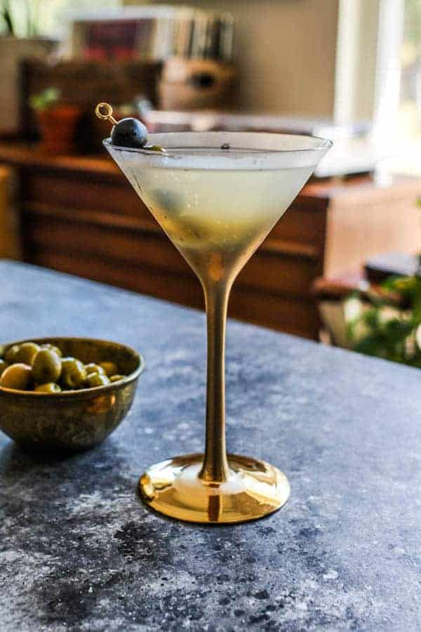 A Classic Vodka Martini on a table top next to a bowl of green olives