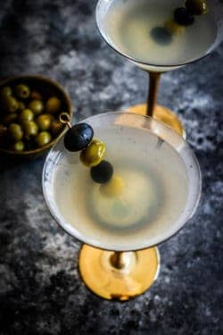 2 chilled martini glasses filled with Classic Vodka Martinis. Each has a skewer with alternation black and green olives.