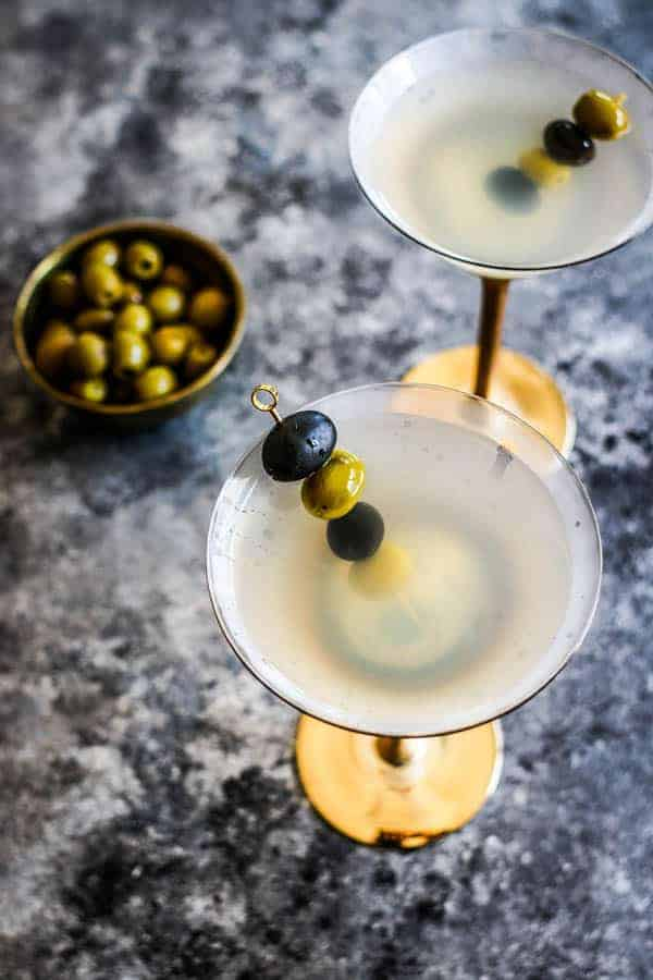 Two Classic Vodka Martinis next to a bowl of olives