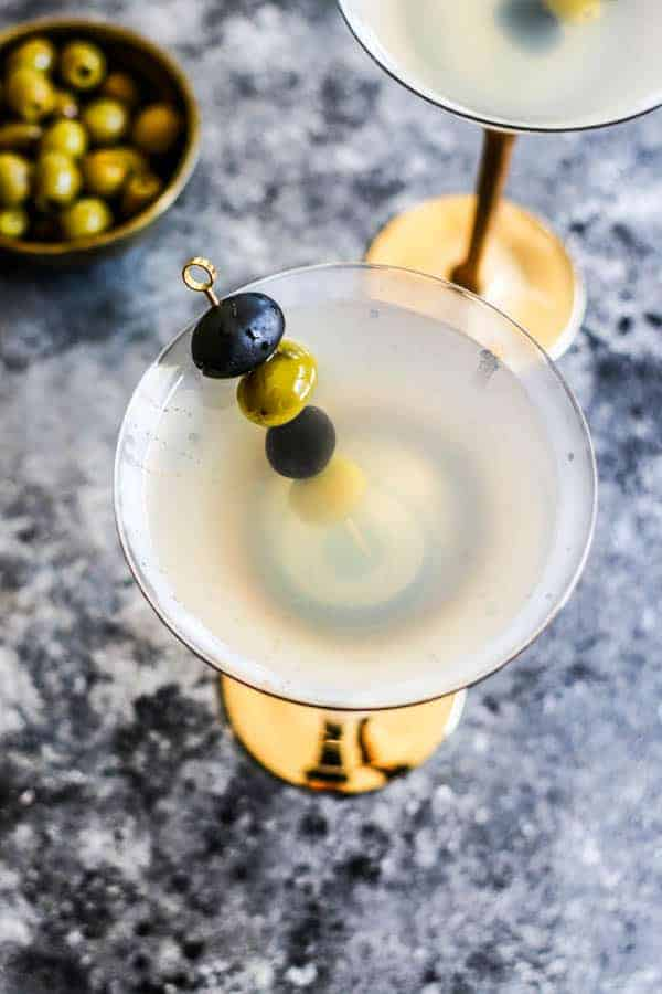 Top down image of a Classic Vodka Martini with a pick of black and green olives next to a bowl of olives.