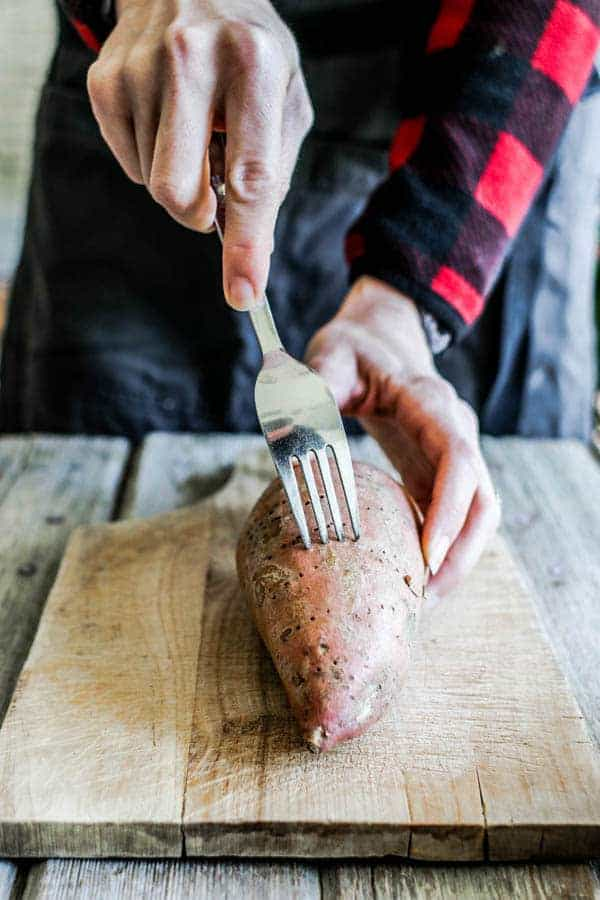A woman poking holes in a sweet potato with a fork
